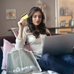 A woman holding a credit card and looking at her credit score on a silver laptop